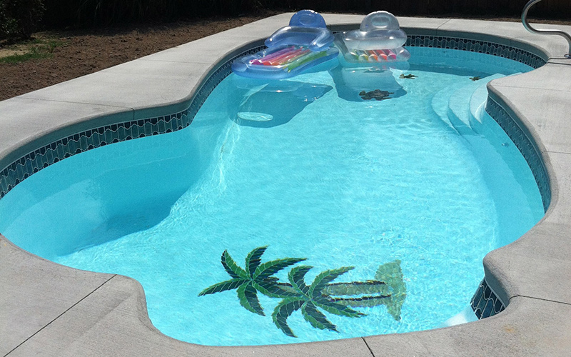 Alaglas Pools' Malibu, a medium, freeform fiberglass pool in white with tile mosaics