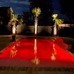 Alaglas Pools' Majestic model, a large, rectangular shaped pool in quartz at night with LED lighting