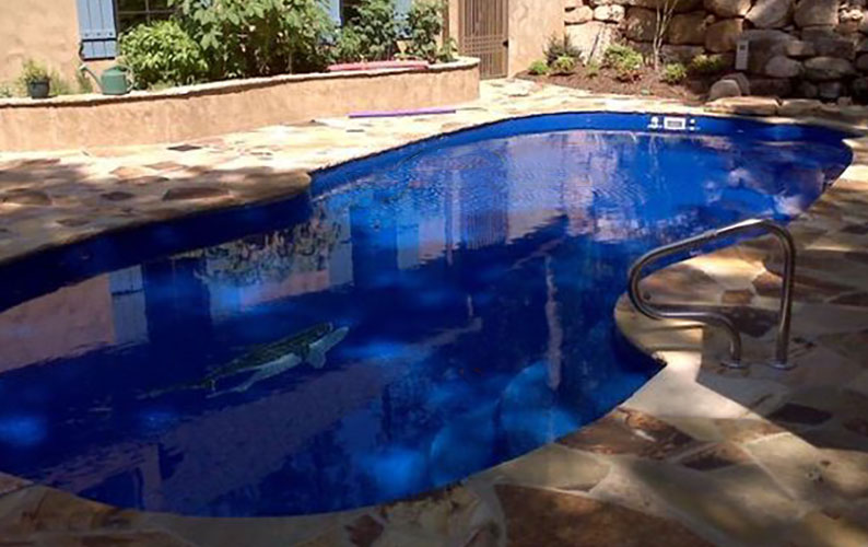 Alaglas Pools' Grand Baron, a large, freeform fiberglass pool in sapphire blue